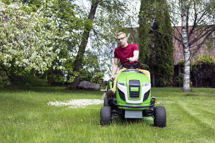 Young man, gardener driving ride on mower. Mowing grass in yard, tractor. Gardening. Backyard Blooming Countryside Garden Gardener Gardening Gras Cutting Grass Grass Cutter Home Lawn Lawn Mower Lawn Mowing Lawnmower Man Mower Mowing Mowing Tractor Nature One Person Outdoors Riding Mower Spring Tractor Yard