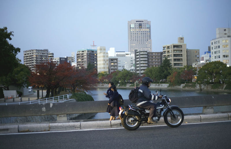 People riding motorcycle on road against cityscape
