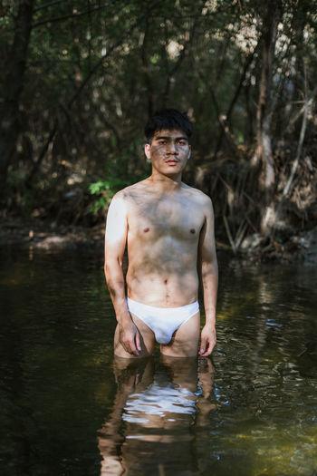 Portrait of shirtless man standing in lake