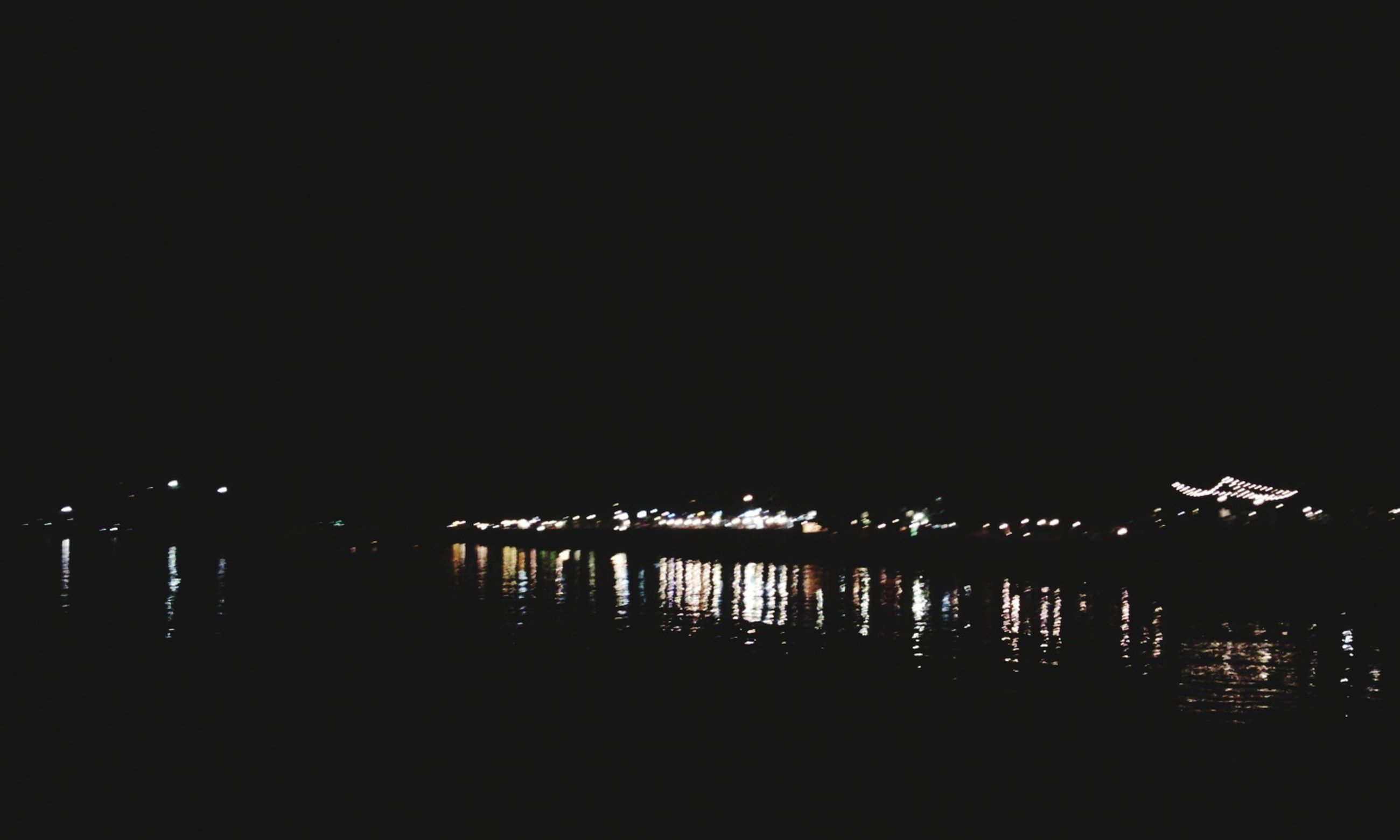 night, water, illuminated, copy space, reflection, dark, clear sky, silhouette, river, tranquility, waterfront, tranquil scene, sea, built structure, lake, nature, scenics, sky, pier, architecture