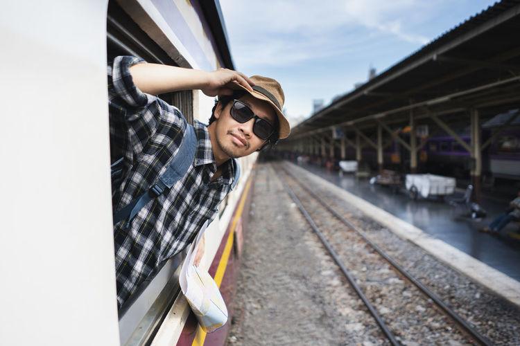Passenger wearing sunglasses peeking through train window