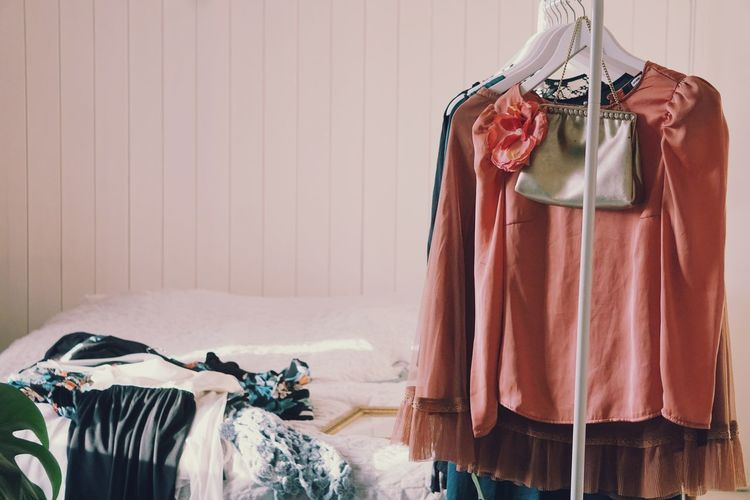 Clothes Hanging On Rack Against Wall At Home