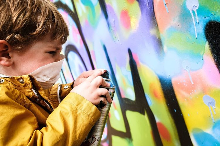 Graffiti Multi Colored Spray Paint Art And Craft Creativity Artist Males  Street Art One Person Boys Real People Paint Aerosol Can Lifestyles People Portrait Playing Modern Standing Outdoors