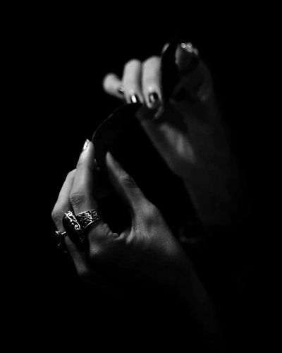 Close-up of man holding hands against black background