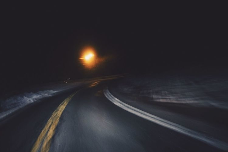 Light trails on road at night during winter