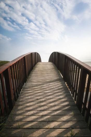 View of empty footbridge against sky