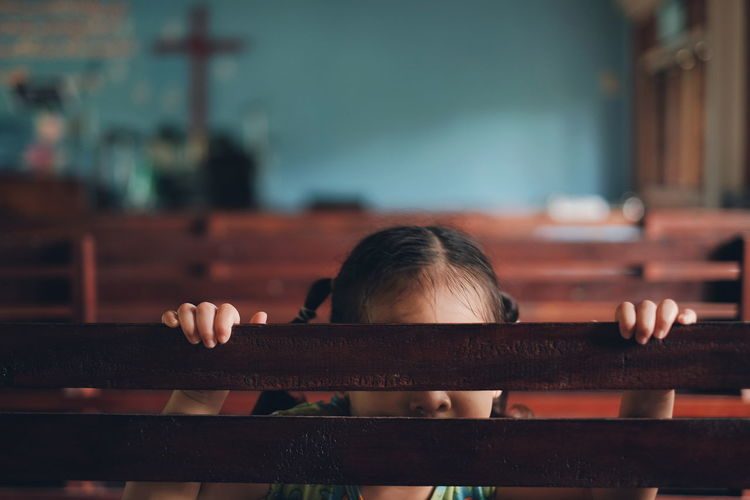 Girl Hiding Behind Pew In Church