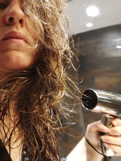 Midsection of woman using hair dryer at home