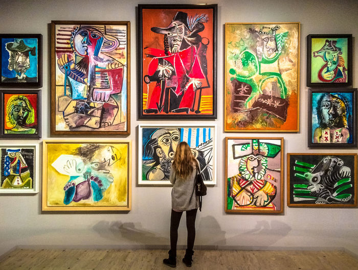 """Taken at the exhibition """"PIcasso Mania"""" in the Grand Palais, Paris, in 2016. It showed Picasso and artists he influenced. The woman is looking at a wall with Picasso paintings from the 1970s hung like Picasso had done at the original exhibition back then. Paintings Picasso Picasso Retrospective Arts Culture And Entertainment Creativity Exhibition Human Representation Indoors  Leisure Activity Multi Colored One Person Painting Painting Exhibition Paintings On The Wall Picasso Mania Standing Variation Young Adult The Week On EyeEm"""