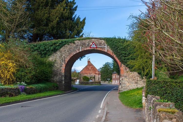 Road seen through arch bridge against clear sky