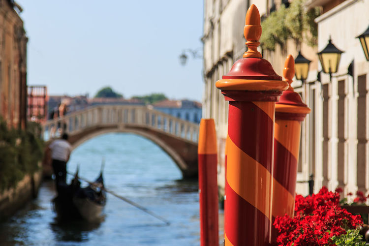 Close-up of red and orange striped poles in grand canal