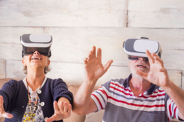 Senior couple wearing virtual reality simulator at home