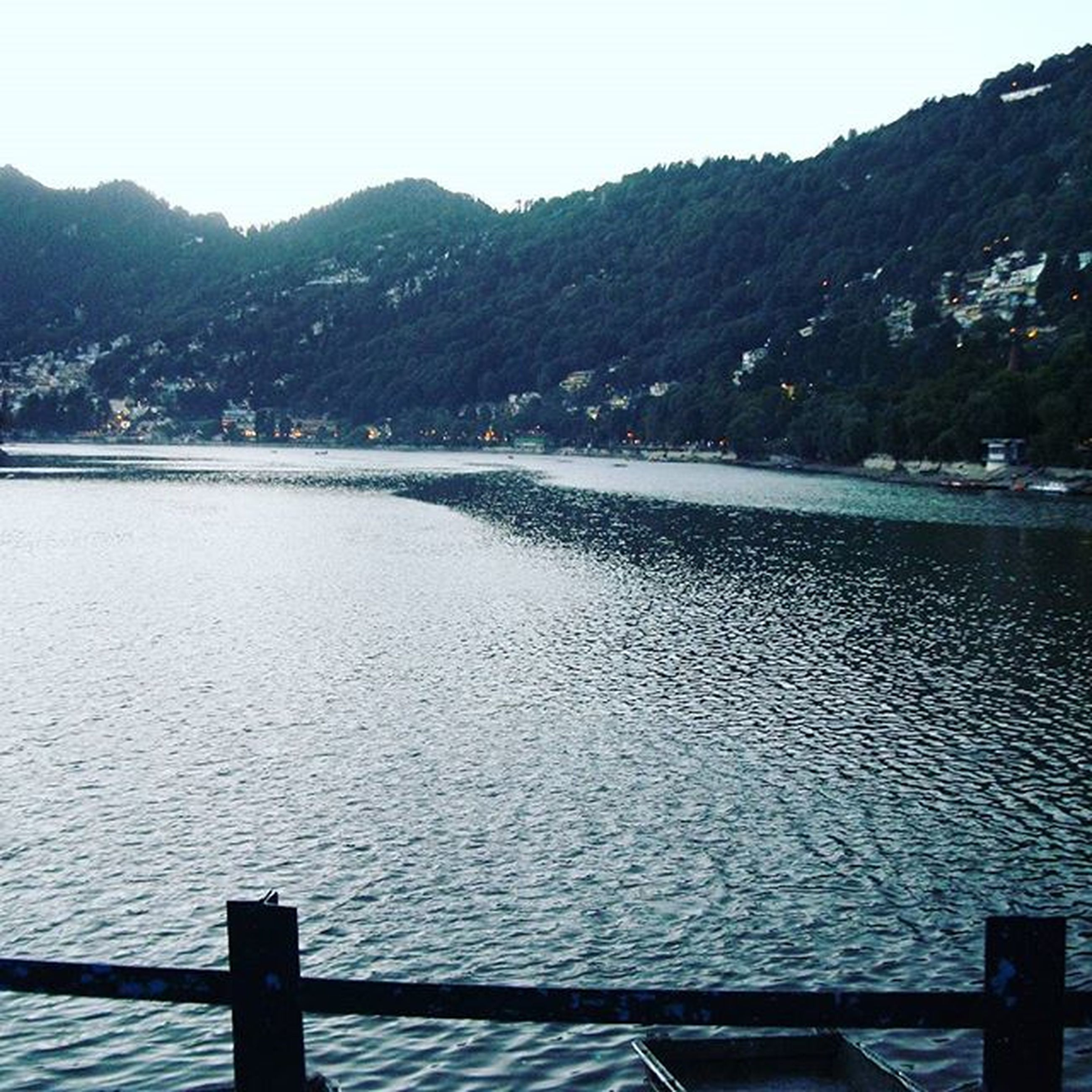 water, mountain, tranquil scene, tranquility, scenics, mountain range, beauty in nature, nature, clear sky, river, rippled, lake, sky, sea, built structure, railing, pier, idyllic, outdoors, day
