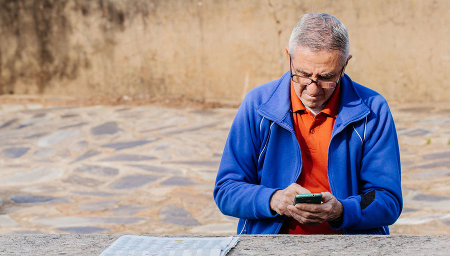 Full length of man holding mobile phone while sitting outdoors