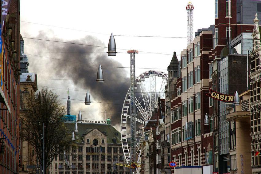 Amsterdam Amusement Ride Amusementpark Architecture Building Exterior Built Structure City City Life On Fire Outdoors Sky Smoke Wheel Adventures In The City