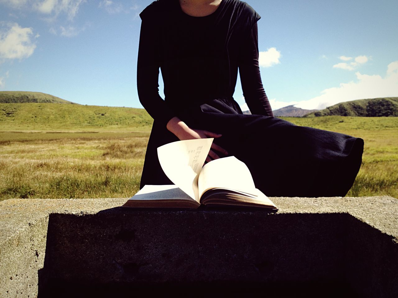 Midsection of woman by retaining wall with book