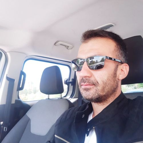 Mid adult man wearing sunglasses while driving car