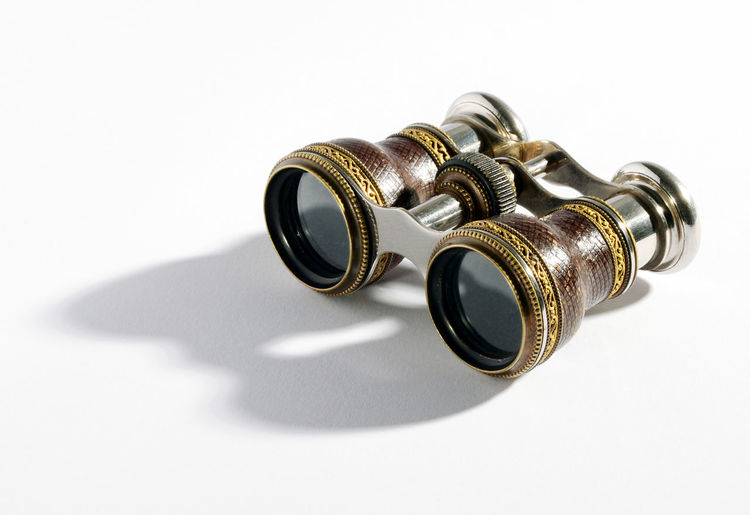 Close-up of old binoculars against white background
