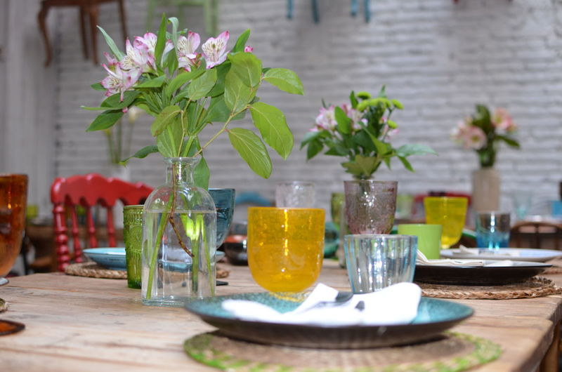 Plants by glasses and plate on table