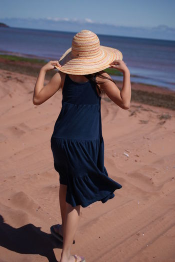 Rear View Of Woman Wearing Straw Hat At Beach