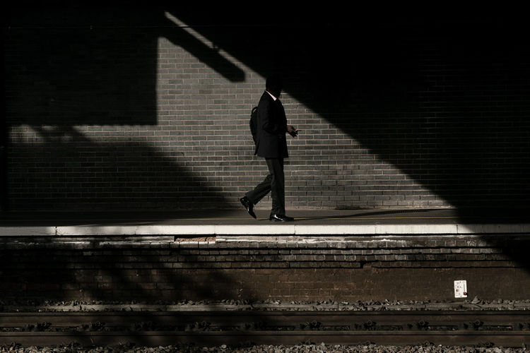 Side view of man walking on railroad station platform
