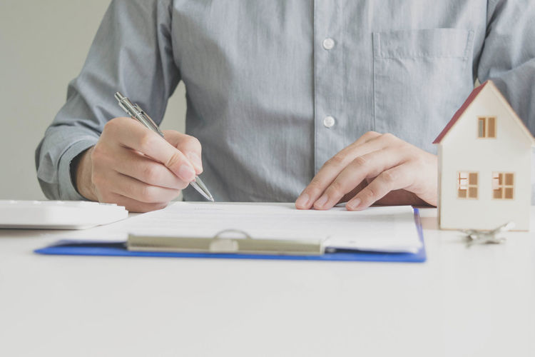 Midsection of client signing document on table