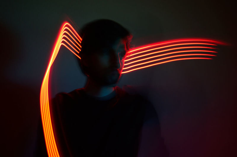 Blurred motion of man standing against illuminated light trails