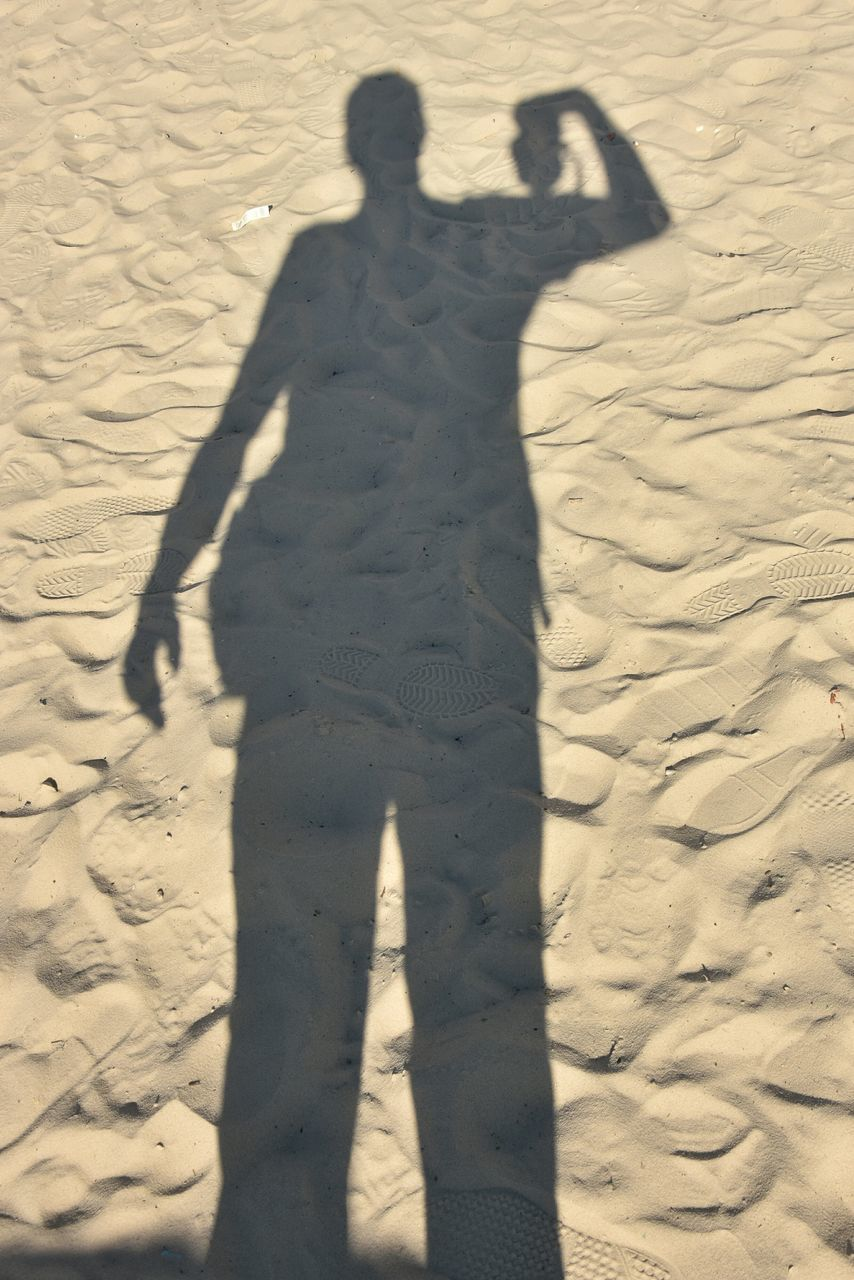 shadow, sand, land, real people, high angle view, sunlight, nature, lifestyles, focus on shadow, leisure activity, beach, one person, day, women, standing, adult, outdoors, child, childhood