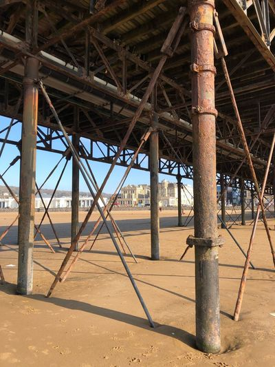 Under the Pier Bridge - Man Made Structure Sunlight Land Day Outdoors Beach Water Sky Sand Architectural Column Rusty