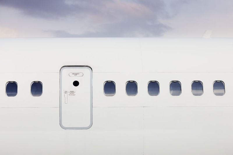 Fuselage of airplane with door and windows. plane against moody sky.