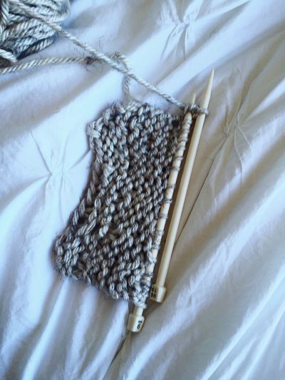High Angle View Of Wool And Needles On Bed