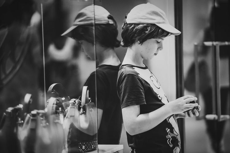 The boy played with a rubic cube while waiting his mother shopping for new handbag. Shades Of Grey Black And White Photography Street Photography Urban Life Reflection Urban Lifestyle Kids Being Kids Live To Learn Untold Stories