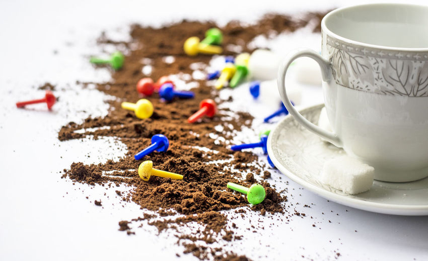 Close-up of coffee powder by cup and saucer on white table