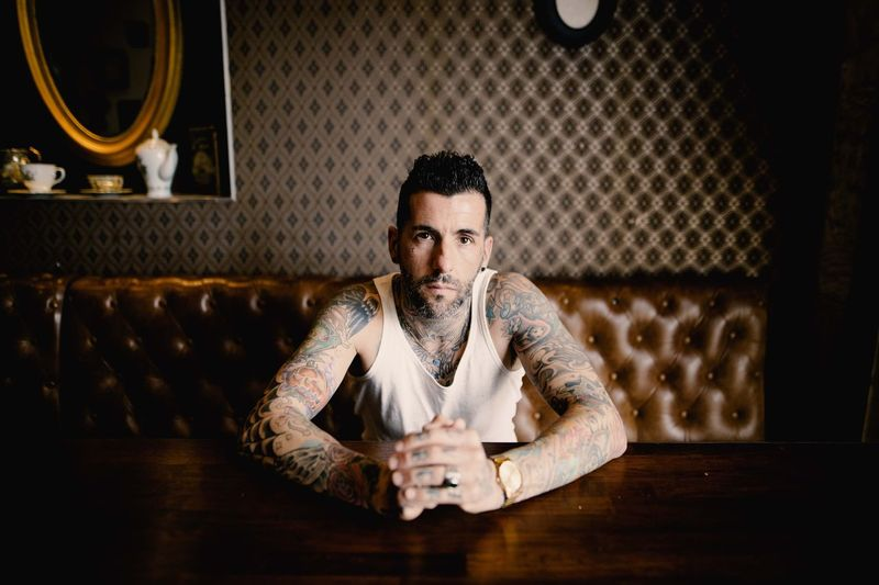 Portrait Of Man With Tattoo Sitting On Sofa At Table