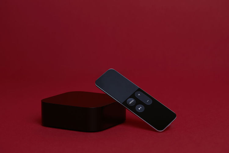 Black Digital Media Player with Remote on a Red Background Red Black Color Studio Shot Indoors  No People Colored Background Close-up Copy Space Technology Connection Arts Culture And Entertainment Still Life High Angle View Communication Smart Phone Cut Out Wireless Technology Two Objects Portable Information Device Table Power Supply