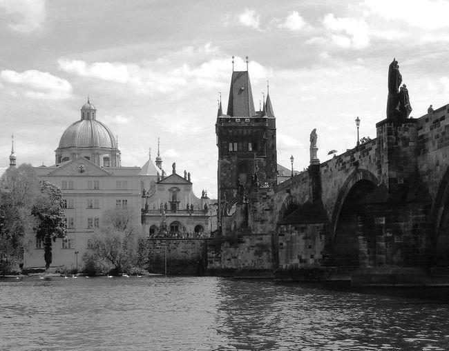 Charles bridge over vltava river in city against sky