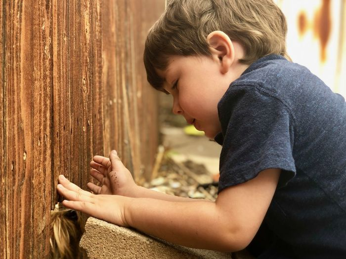 Cute boy looking at dog against wall