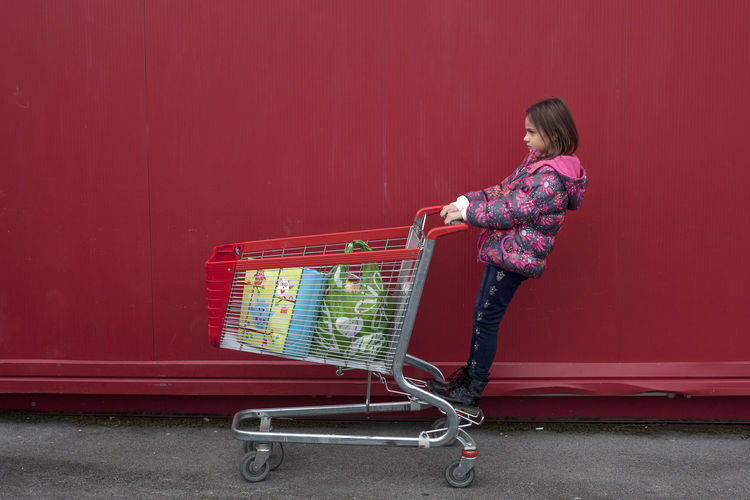 Cart Red Red Color Red Cart Full Length One Person Shopping Cart Childhood Child Casual Clothing Standing Shopping Store Pushing Girls Consumerism Females Retail  Supermarket Side View Hairstyle Innocence Groceries Shopping Fun Streetwise Photography