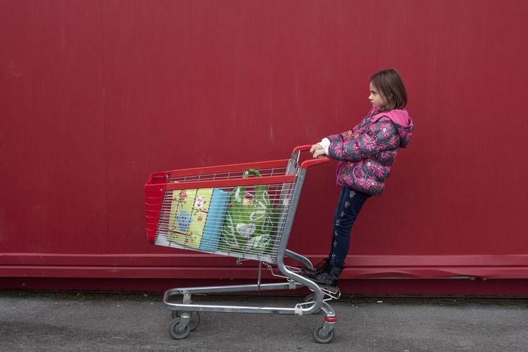 Full Length Of Girl Standing On Shopping Cart Against Red Wall