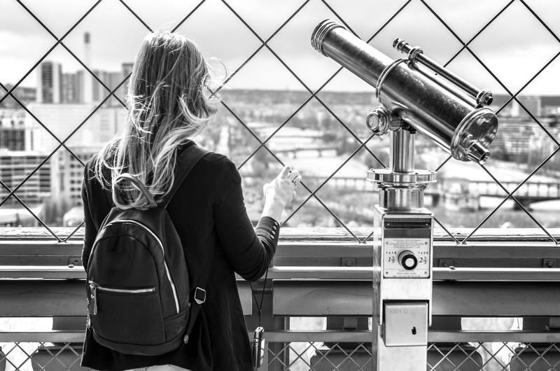 Rear view of a woman standing by a telescope on the eiffel tower, paris