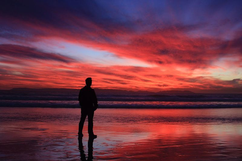 Full Length Rear View of Man Standing At Beach During Sunset