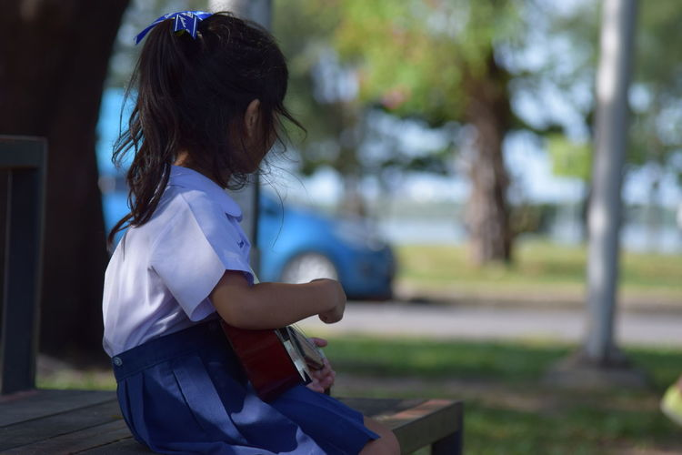Side view of girl playing ukulele while sitting on bench