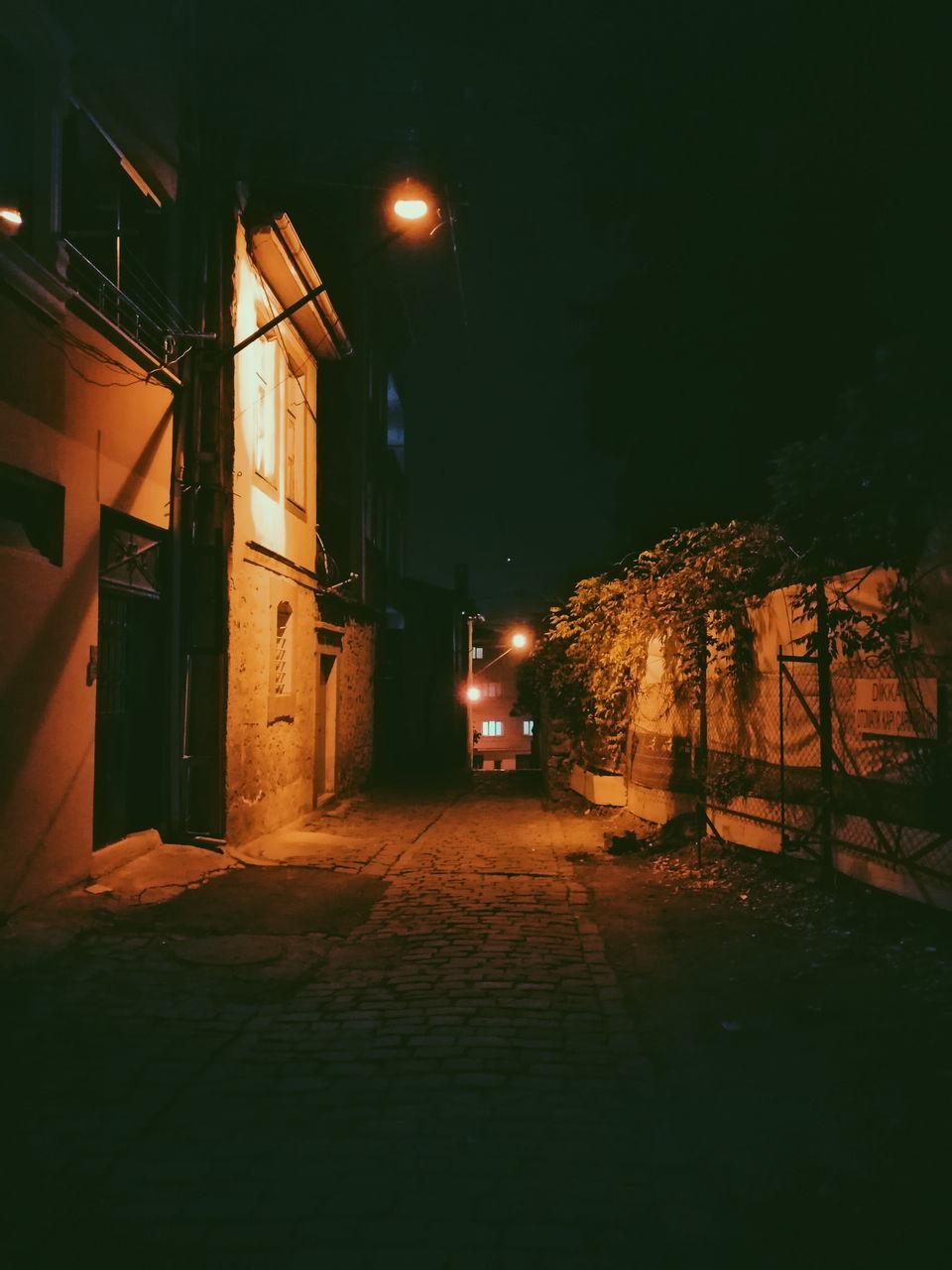 ILLUMINATED STREET LIGHTS BY BUILDINGS AT NIGHT