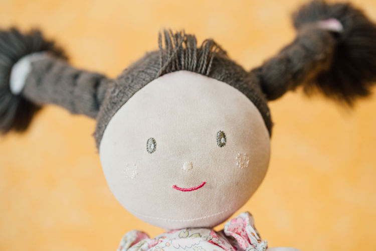 Close-Up Of Female Stuffed Toy Against Yellow Wall