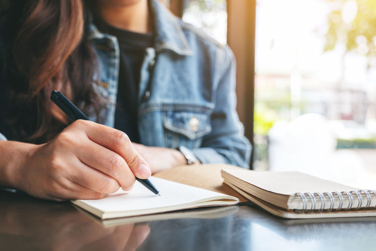 Midsection of woman writing in note pad