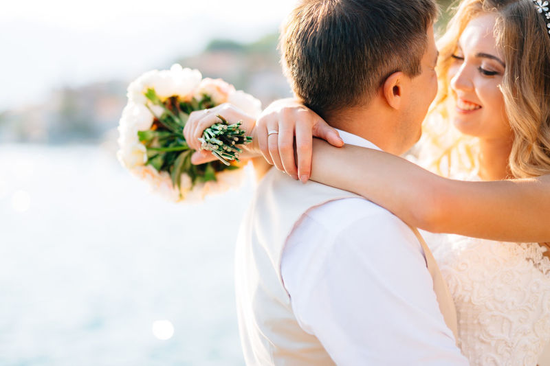 Close-up of couple holding flower bouquet