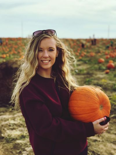 Portrait of smiling young woman holding pumpkin standing in field