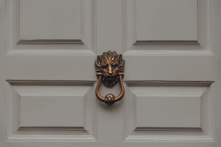 Close up of a lions head door knocker on a front door of a typical british house, uk.