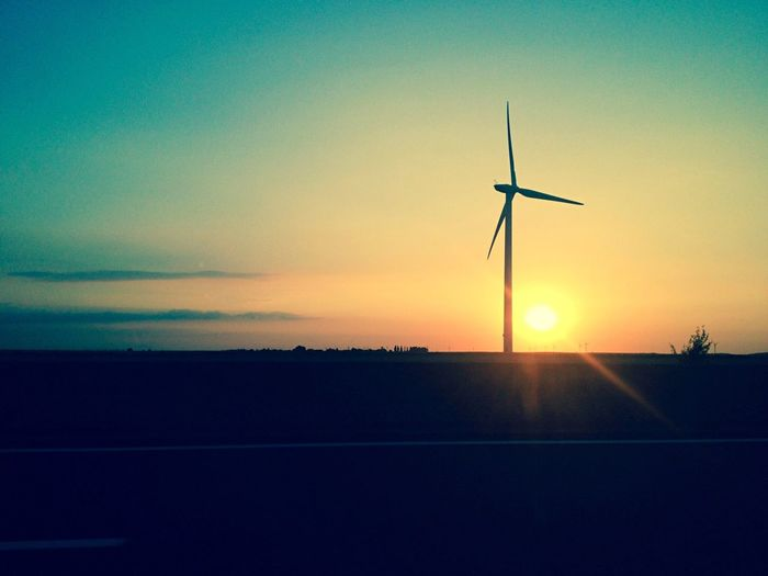 Wind turbines on landscape at sunset