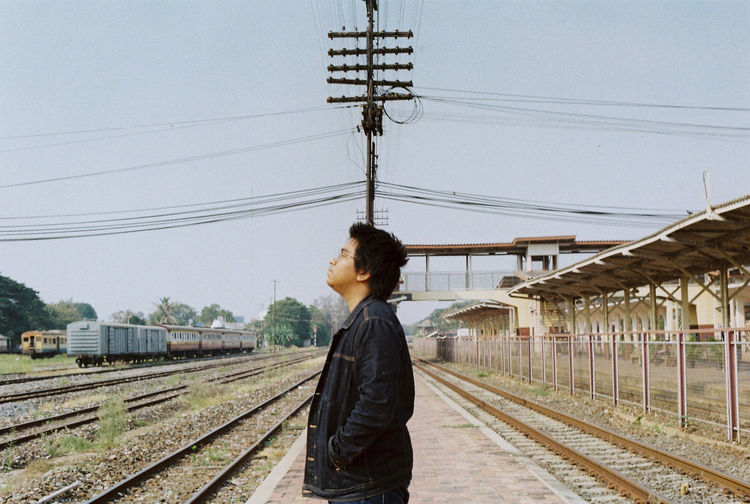 Side view of man standing at railroad station against sky